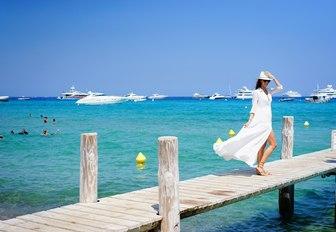 female charter guest strolls along jetty of Le Club 55, St Tropez, France