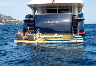 charter guests relax on floating pontoons aboard luxury yacht MISCHIEF