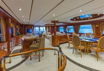the luxurious and deluxe lounge with sophisticated seating and dining space as well as cocktail bar on charter yacht quintessa