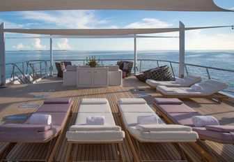 Sun deck with loungers and sofa on board superyacht DREAM, complete with views over the sea