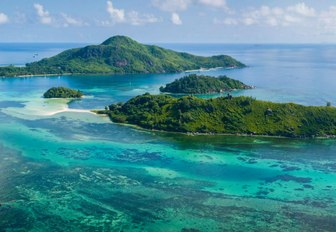 Green jungle islands in the Seychelles, with blue sea surrounding