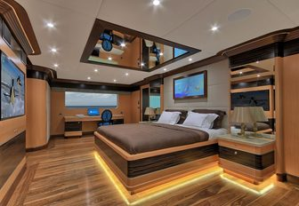 large bed in the wood-clad master suite on board charter yacht MEIRA