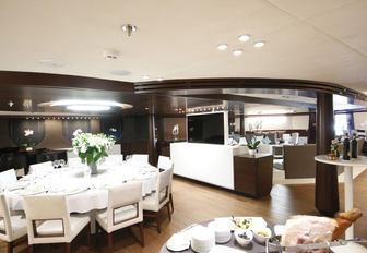 circular dining table forms the indoor dining area on board motor yacht KATINA
