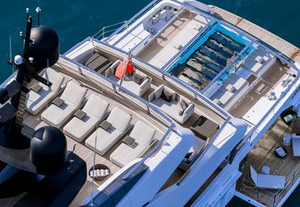 the three aft decks of charter yacht lady lena with sun loungers, glass bottom infinity pool, and platform side decks