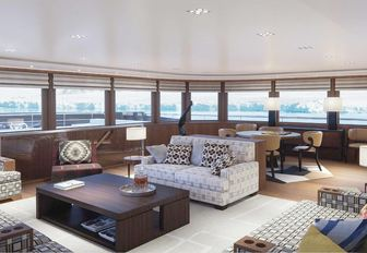 main salon with sofas and table and chairs on board charter yacht Planet Nine