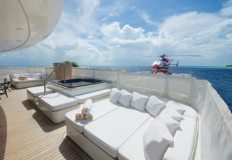 helicopter lands on helipad with Jacuzzi and sunpads in shot on board superyacht SENSES