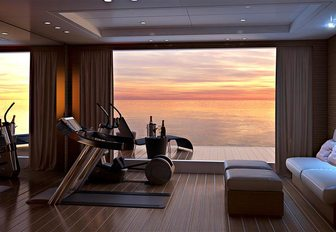 sun setting in background as seen from beach club on benetti charter yacht spectre, which features gym equipment