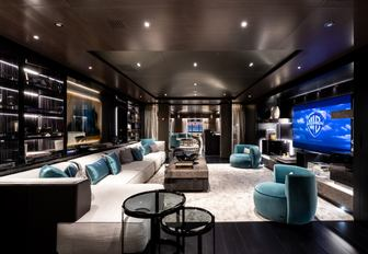 large white sofa faces huge TV screen in the main salon aboard motor yacht SOLO