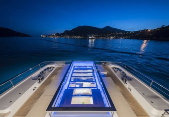 A swimming pool lit up at night on board a superyacht