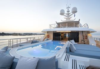 large pool surrounded by sun pads on the flybridge of luxury yacht O'PTASIA