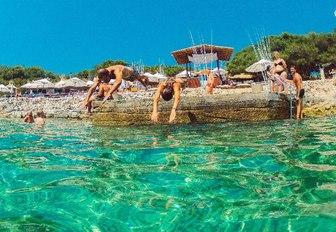 visitors at Carpe Diem Beach dive into turquoise waters in Hvar, Croatia