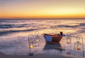 copper bath on the beach on thanda island, surrounded by candles with sun setting on horizon