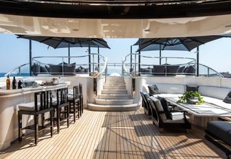 bar and seating area with steps up to pool on sundeck of luxury yacht Silver Angel
