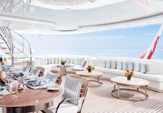 al fresco dining table and built-in sofas on the upper deck aft of charter yacht Lady E
