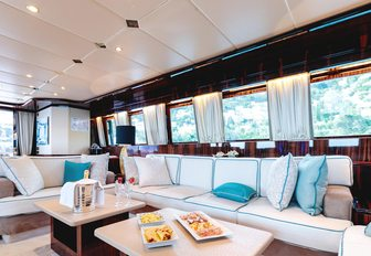 Main salon of superyacht HEMILEA, with white sofas with turquoise cushions and wide windows to let light in