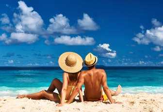 couple relax on white sand beach of the seychelles on their luxury yacht charter