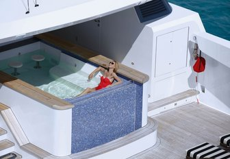 charter guest relaxes in pool aboard charter yacht SOVEREIGN