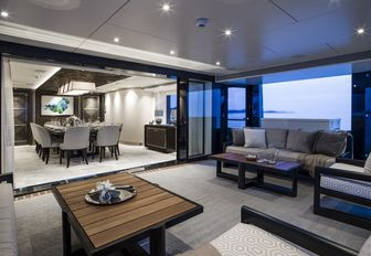 winter garden with comfortable sofas leads into a dining salon on board motor yacht Irisha