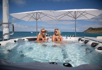 charter guests relax with a cocktail in the spa pool on board motor yacht TRENDING