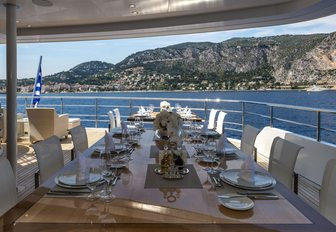 Alfresco dining option onboard SERENITY, elaborate table presentation looking out over raised terrain and sea.