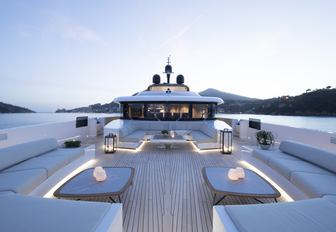 the spacious and minimalist sundeck on superyacht lady lena with a breathtaking view of the Mediterranean surroundings while guests enjoy their charter vacation in summer 2020