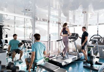 guests ona  luxury yacht charter keeping up with their gym and fitness routine in charter yacht titania well equipped gym