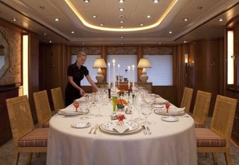 crew member sets dining table for a formal occasion aboard charter yacht OASIS