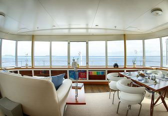 sofa and table and chairs look out to sea in a salon aboard superyacht SENSES