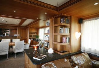 Bookshelves in main salon with formal dining in background on luxury yacht DARDENELLA