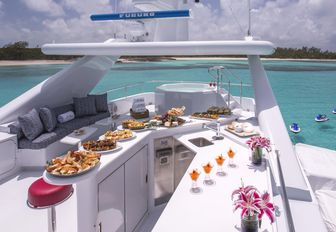 Sun deck with bar and jacuzzi and seating on board charter yacht At Last