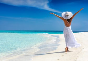 woman dressed in white walks by a Caribbean coast with her arms stretched to the sky in pure serenity while on a luxury yacht charter vacation