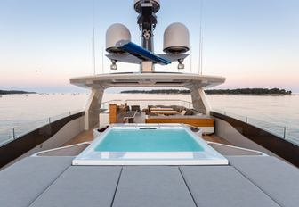 A Jacuzzi as well as sunpads and a bar on board the sundeck of superyacht VERTIGE
