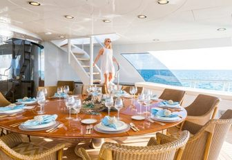 The charter guest on board Amarula Sun during her luxury yacht charter vacation stepping down from her time sunbathing in the sundeck comes down to the alfresco dining area where she will be served a meal by the on board chef