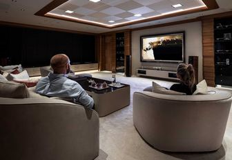 Cinema room on Superyacht LANA with two people in large chairs looking at screen