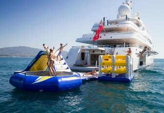 charter guests play on the inflatable water toys on board superyacht TITANIA