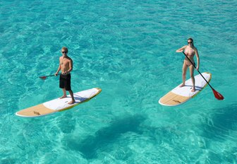 charter guests try out the paddle boards on board motor yacht Sweet Escape