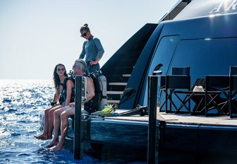 Two guests sitting and one guest standing on the outside of superyacht ARBEMA, with feet dangling above clear sea