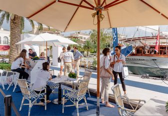 attendees stop for a chat under the shade at the MYBA Pop-Up Show