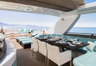 table is set for dinner under the retractable sunroof on the sundeck aboard luxury yacht CRISTOBAL