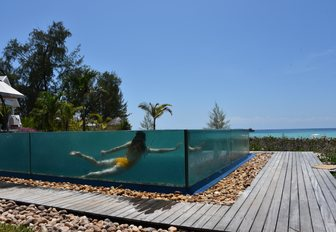 shot of woman underwater through glass of infinity pool on luxury private island, Thanda Island, in East Africa