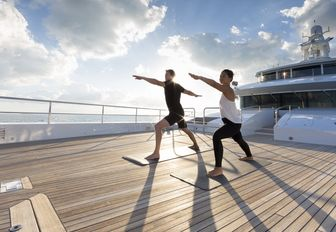 charter guests do yoga on the foredeck aboard motor yacht NAUTILUS