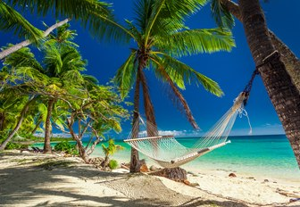 hammock tied up between two palm trees on a white sandy beach in Fiji