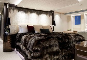 large bed with faux fur throw in the master suite aboard luxury yacht Irisha