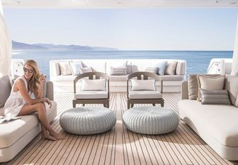 charter guest relaxes on the main deck aft with its sheer curtains on board charter yacht TURQUOISE