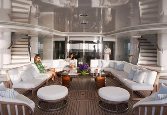 charter guests sit on comfortable sofas on the aft deck of luxury yacht Lady E