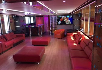 red leather seating illuminated by colourful lighting in the skylounge aboard charter yacht Code 8