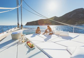 guest in the Jacuzzi aboard sailing yacht Q chats to a guest on the sunpads nearby
