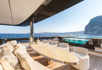 poolside shot of al fresco dining area and glass bottom infinity pool of luxury yacht Icon