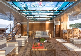 the spacious and airy beach club of crewed yacht lady lena illuminated by the glistening light that poors in through the glass bottom swimming pool that hovers over head and the extendeable side platforms on the side of the space