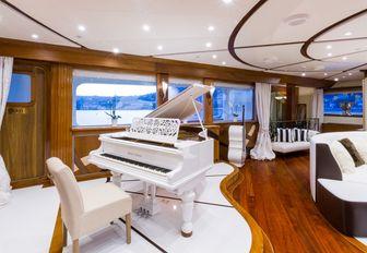 white grand piano in the main salon of charter yacht LEGEND